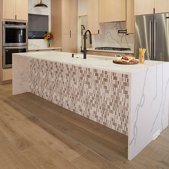 An open format kitchen with wood look tile on the floor and a marble island with random mosaic on the front of the island