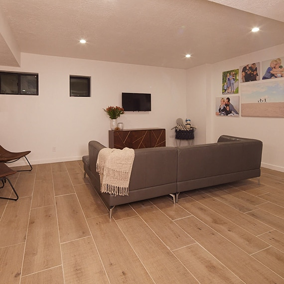 Basement family room with light colored wood look tile floor