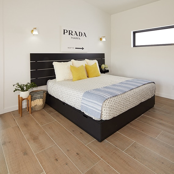 Bedroom with light colored wood look tile on the floor with contemporary furnishings