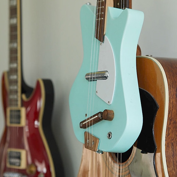 Close up of a collection of acoustic and electric guitars displayed on the wall