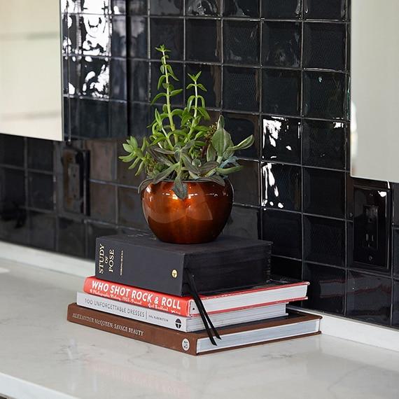 Close up of bathroom vanity with glossy black square ceramic tiles on the backsplash