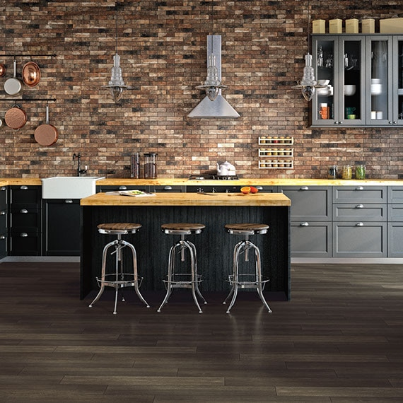 Industrial style kitchen with brick look tile on the backsplash with a large island with metal stools