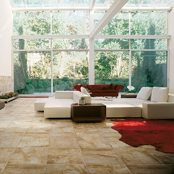 Beautiful open living area with large windows big sofas and veined stone look tile