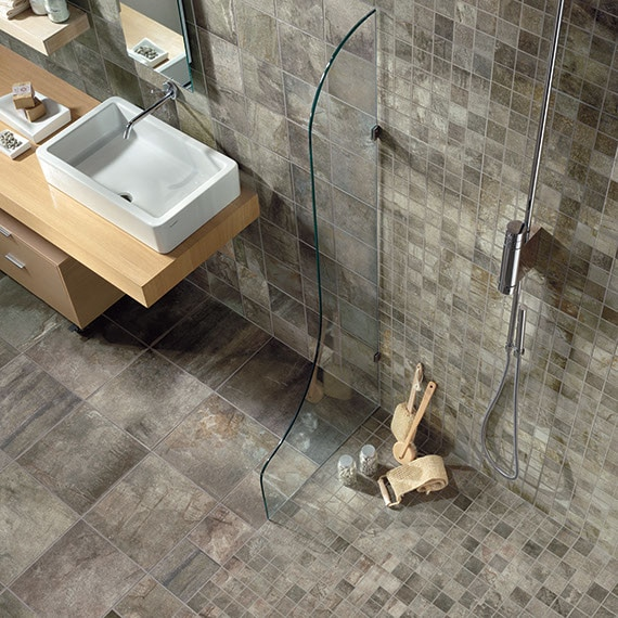 Close up of zero entry shower floor in gray stone look tile in two sizes: a mosaic and 12 by 12 on the bathroom floor