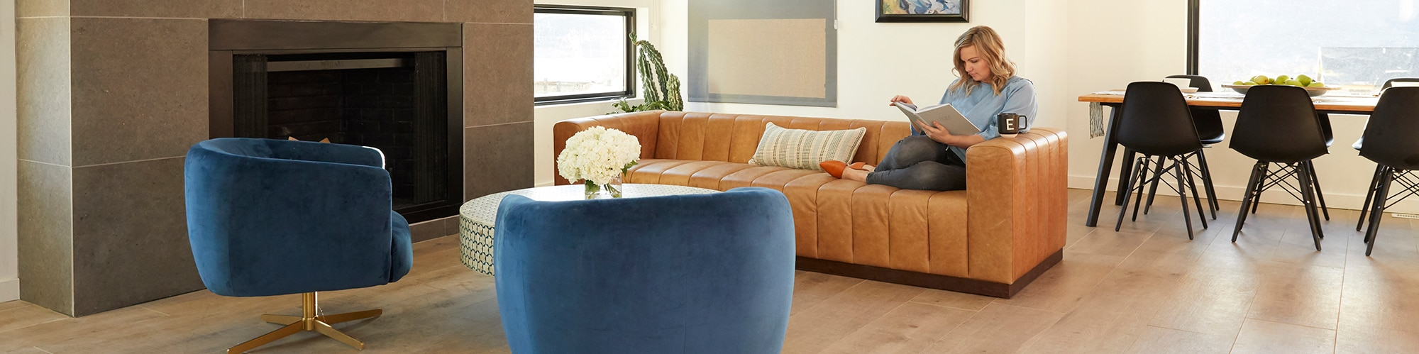 Open format living room with tiled floor and fireplace. Woman sitting on couch reading a book