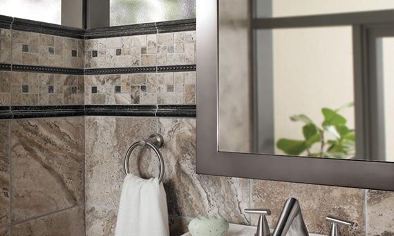 Bronze metal look tile behind a contemporary bathtub faucet with metal look bronze trim