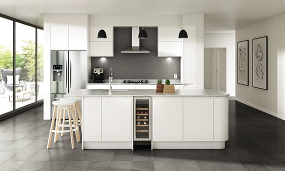 Open modern white kitchen with gray accent wall and gray swirl limestone look tile